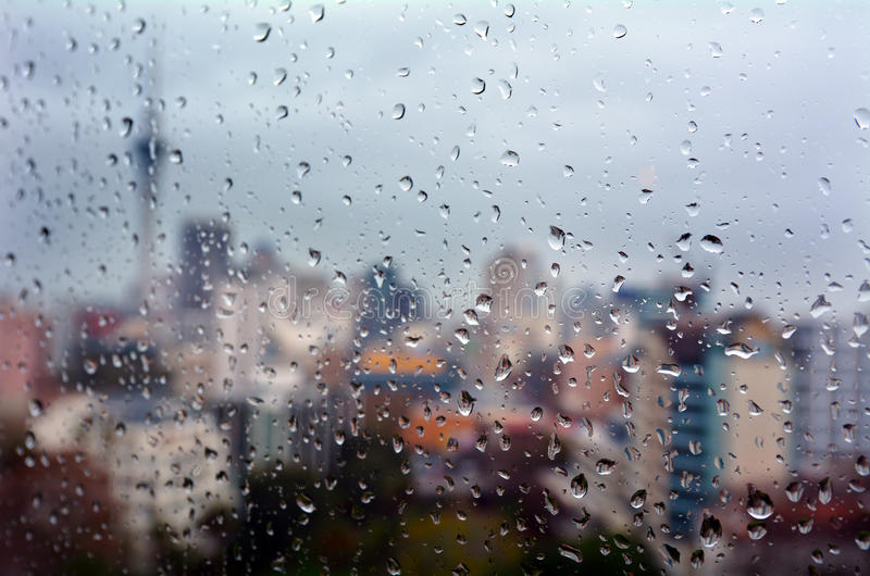 La pluie laisse tomber des chutes sur une fenêtre donnant sur Auckland CBD nouveau Zealan photos libres de droits