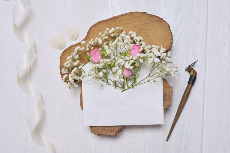 La pluma caligráfica un sobre con las flores subió y una letra fotografía de archivo