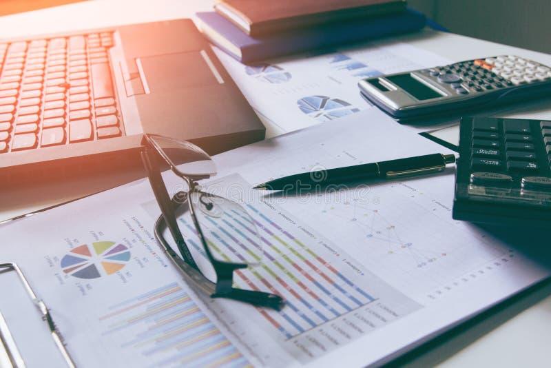 La pluma con los gráficos de negocio y las cartas divulgan, calculadora en el escritorio del cepillado financiero Extracto financ foto de archivo libre de regalías