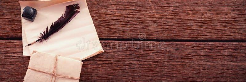 La pluma de canilla, el pote de la tinta, y los documentos jurídicos arreglaron en la tabla foto de archivo libre de regalías