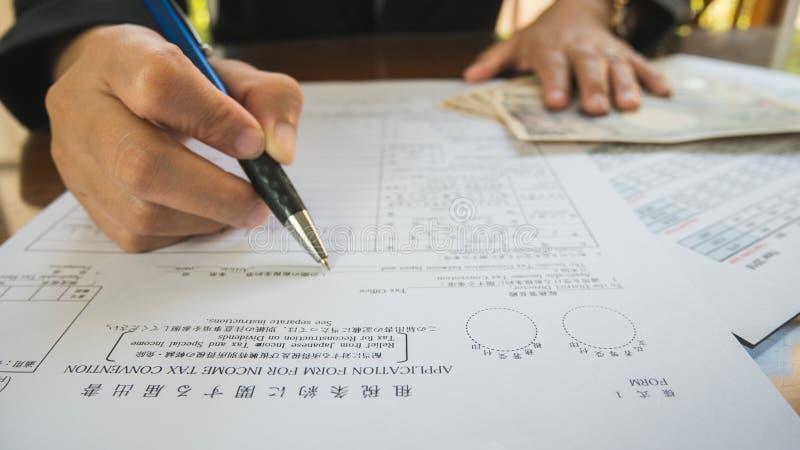 La pluma del control de la mano de la mujer de negocios completa los detalles en el papel de formularios de impuesto en concepto  foto de archivo libre de regalías