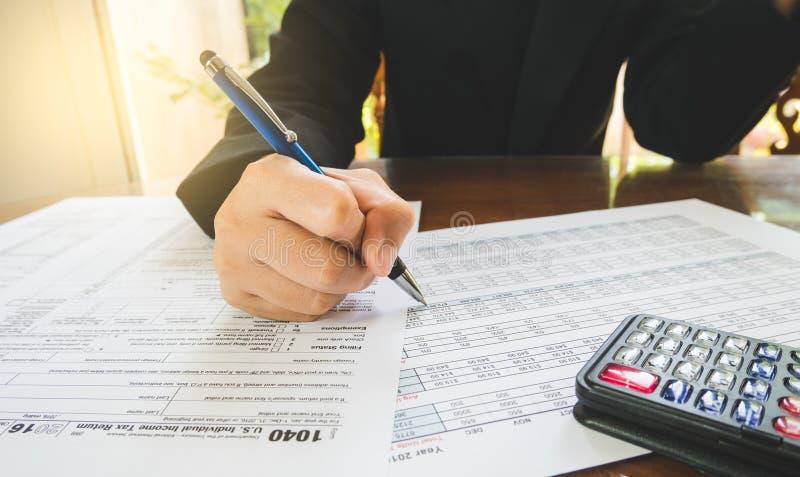 La pluma del control de la mano de la mujer de negocios completa los detalles en el papel de formularios de impuesto en concepto  imagenes de archivo