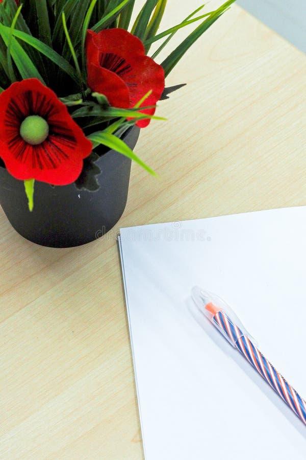 La pluma en el papel en blanco al lado del pote de la flor falsa puso la tabla de madera imágenes de archivo libres de regalías