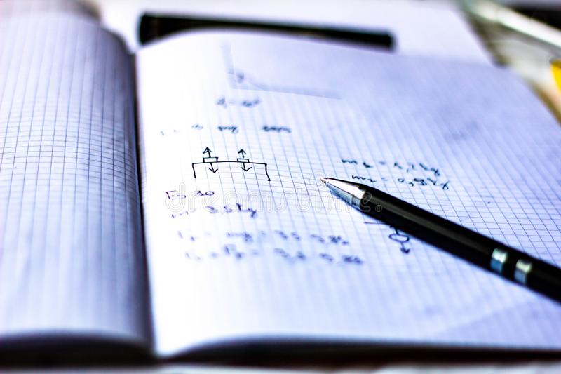 La pluma en un cuaderno con los cuadrados escritos con fórmulas, escuela comienza en septiembre, ahora él es apenas un rato corto foto de archivo libre de regalías