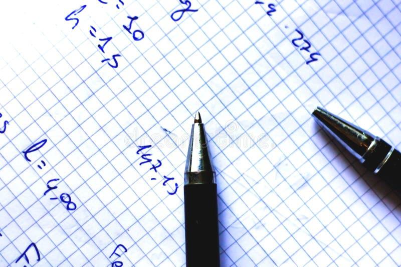 La pluma en un cuaderno con los cuadrados escritos con fórmulas, escuela comienza en septiembre, ahora él es apenas un rato corto imagen de archivo libre de regalías