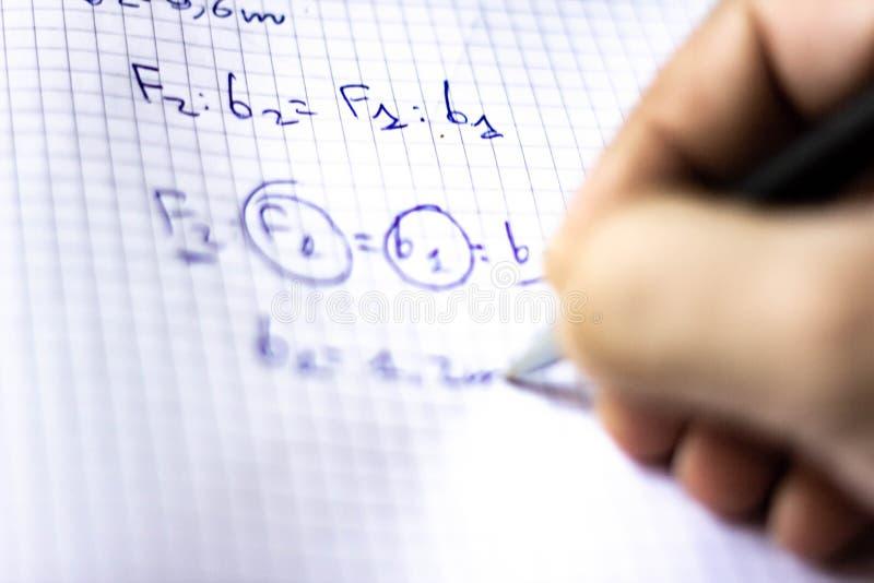La pluma en un cuaderno con los cuadrados escritos con fórmulas, escuela comienza en septiembre, ahora él es apenas un rato corto foto de archivo