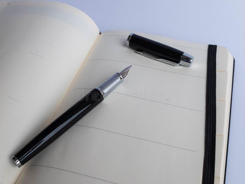 La pluma negra del negocio del metal miente dentro del cuaderno abierto con las páginas en blanco fotos de archivo