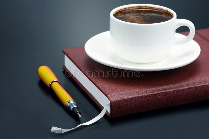 La pluma roja es una taza del platillo de caf? s?lo. Art?culos de la oficina fotos de archivo libres de regalías