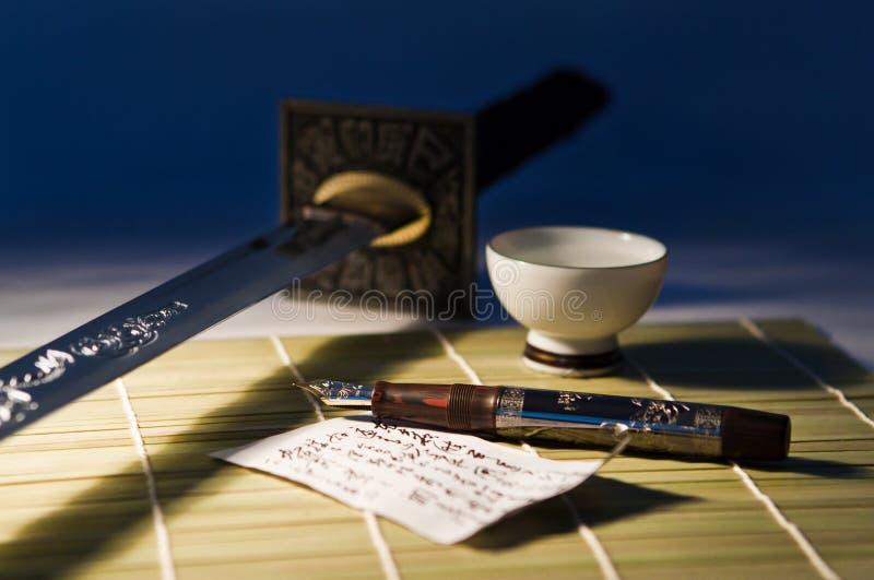 La pluma y la espada foto de archivo