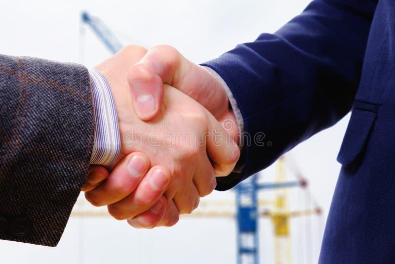 La poignée de main de concept, constructeur d'homme d'affaires de conclusion de contrat, regardant le site de ville de constructi photos stock