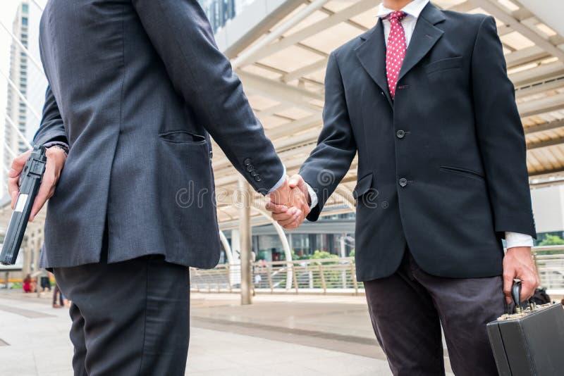 La poignée de main de deux hommes d'affaires sont malhonnête et fraude avec se tenir photo libre de droits