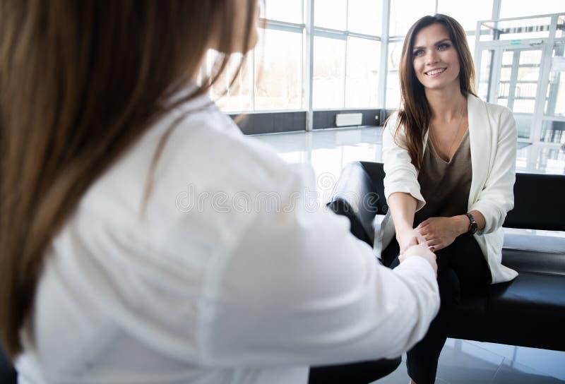 La poignée de main de sourire de collègues de femmes d'affaires dans le bureau, faisant l'affaire lors de la réunion, directeur s images stock