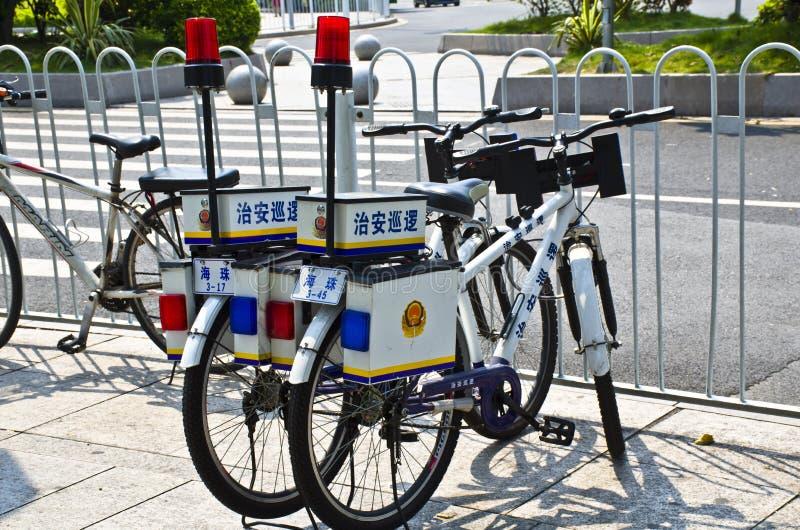 La policía china monta en bicicleta en la calle imagenes de archivo