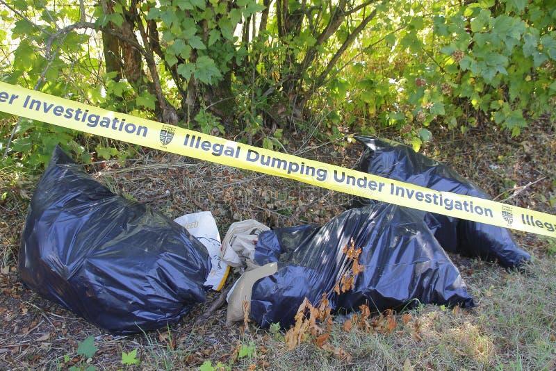 La policía graba y descarga ilegal de la basura fotos de archivo