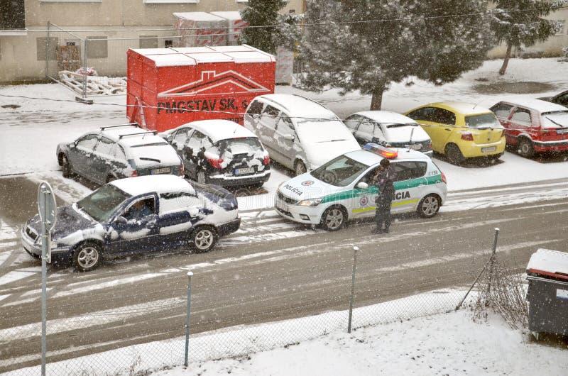 La policía trafica la parada del partol un coche Vehículo exterior del soporte del policía en mún tiempo mientras que cae la niev foto de archivo libre de regalías