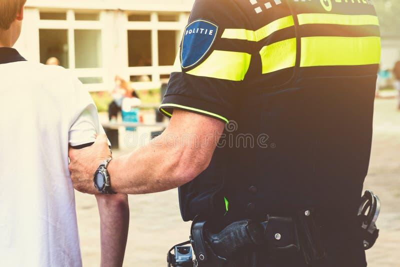 La police arrête un garçon à l'école image libre de droits