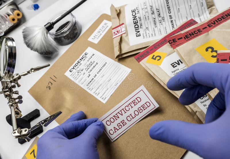 La police que l'expert colle l'autocollant sur le dossier s'est fermée du meurtre dans le scientifique de laboratoire photographie stock libre de droits