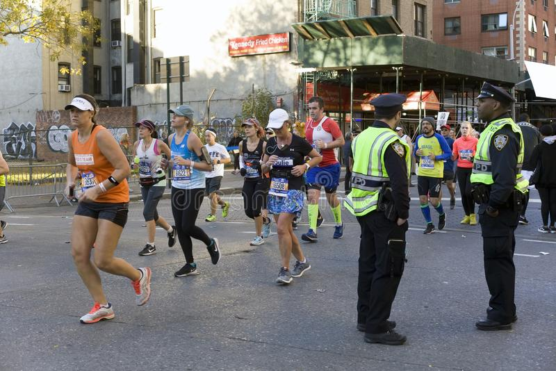 La police regarde pendant que les coureurs à Manhattan participent au marathon de NYC photo stock