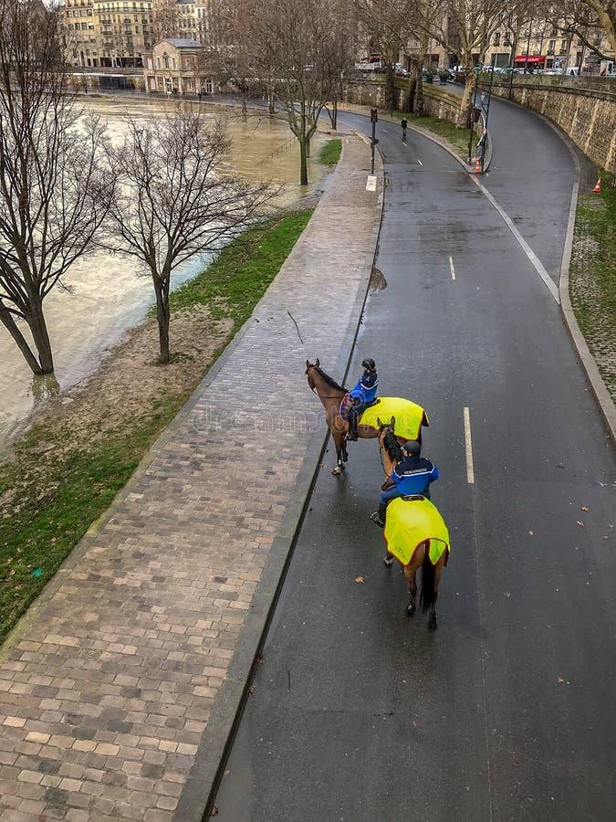 La police sur des chevaux patrouille le DES partiellement inondé de Parc déchire De la Seine, Paris, France photo libre de droits