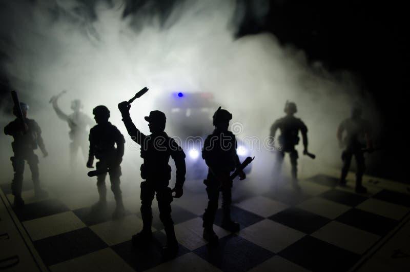 la polizia di Anti-tumulto dà il segnale essere pronta Concetto di potere di governo Polizia sulla scacchiera Fumo su un fondo sc fotografia stock