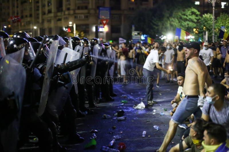 La polizia di tumulto spruzza il gas lacrimogeno mentre si azzuffa con i dimostranti immagine stock libera da diritti