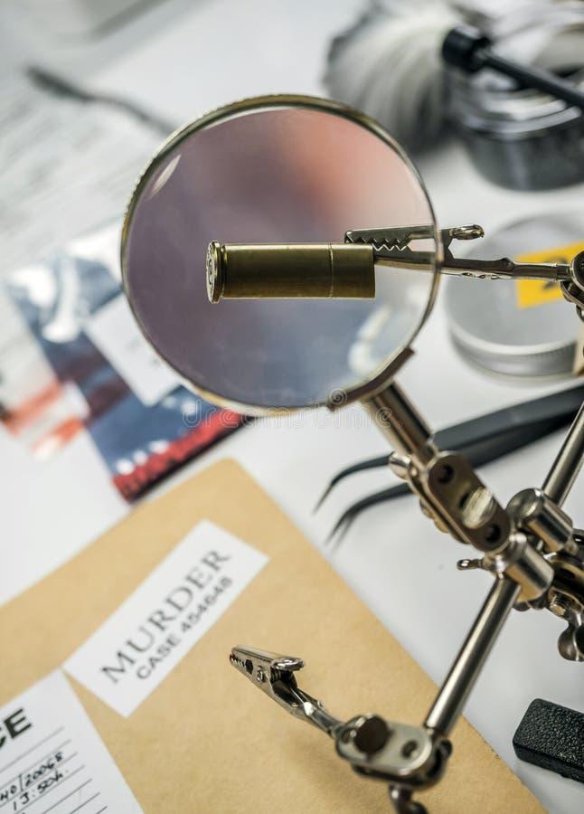 La polizia esperta esamina un cappuccio della pallottola in laboratorio scientifico con la lente d'ingrandimento fotografia stock libera da diritti