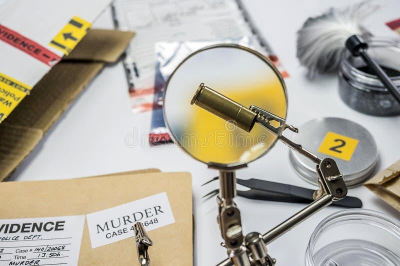 La polizia esperta esamina un cappuccio della pallottola in laboratorio scientifico con la lente d'ingrandimento immagine stock libera da diritti