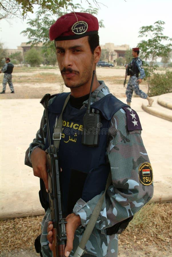 La polizia irachena DÀ UNO SCHIAFFO A con il Kalashnikov immagine stock libera da diritti