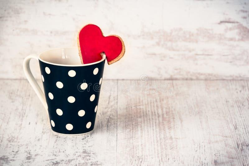 La Polka nera ha punteggiato la tazza di caffè con un biscotto casalingo a forma di cuore sopra fondo di legno bianco immagini stock libere da diritti