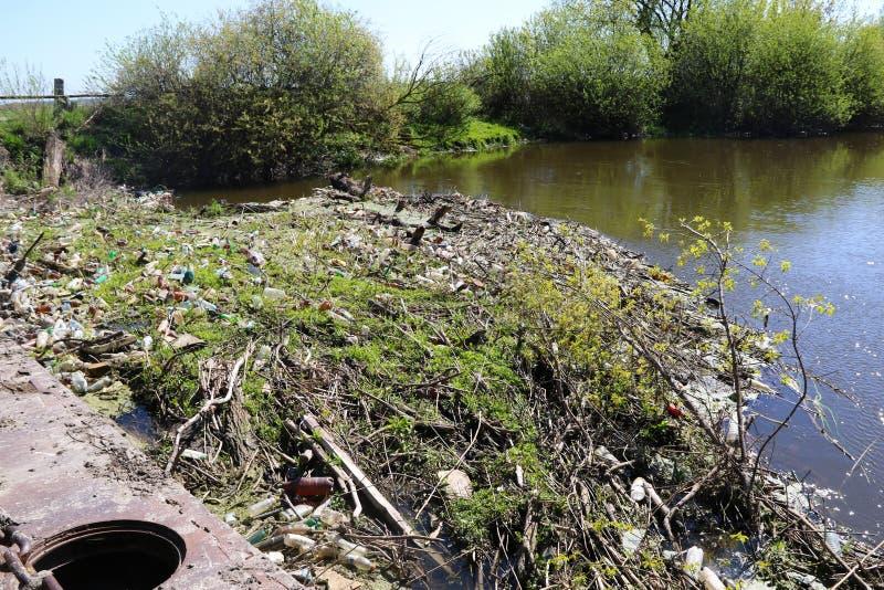 La pollution de l'environnement est un groupe de déchets sur la berge image stock
