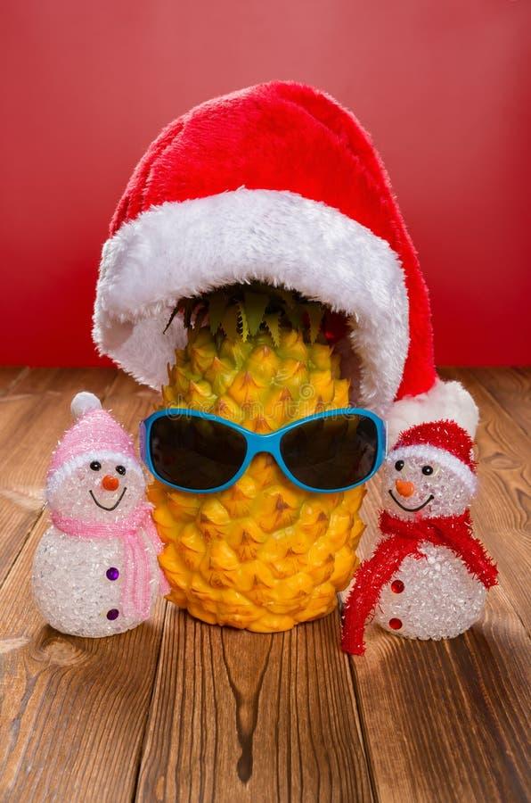 La pomme de pin porte un chapeau du père noël et des lunettes du soleil avec deux bonhommes de neige images libres de droits