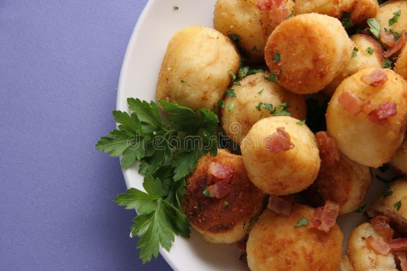 La pomme de terre durcit avec le lard. images stock