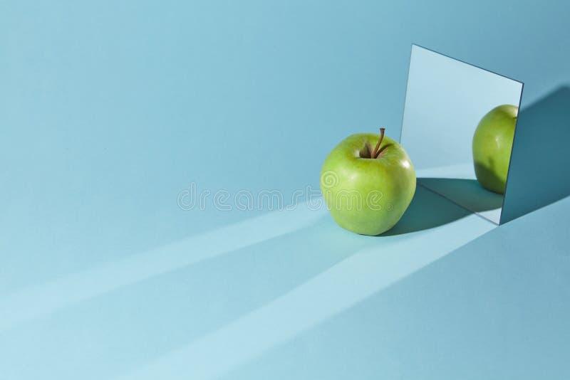 La pomme est vert, un miroir carré sur un fond bleu, une réflexion d'une pomme et des ombres dans un miroir images stock