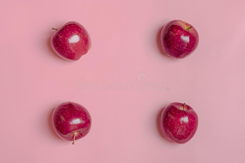 La pomme rouge moissonnée fraîche se trouve sur le fond millénaire de rose de tendance Fruit avec la vitamine C, kératine Organiq photographie stock