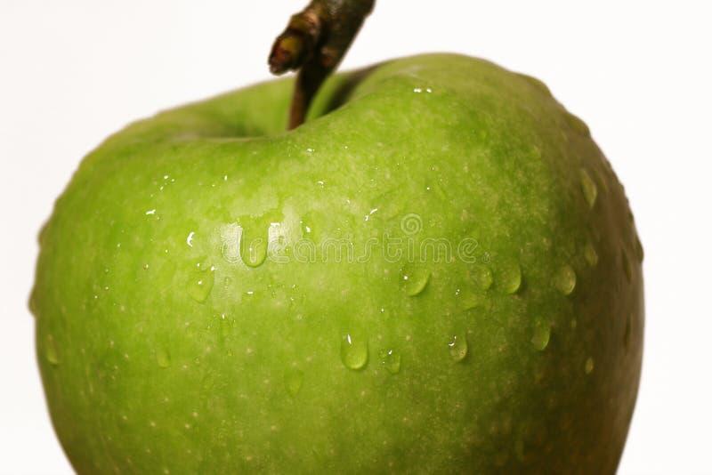 La pomme verte avec de l'eau se laisse tomber sur le fond blanc, macro images stock