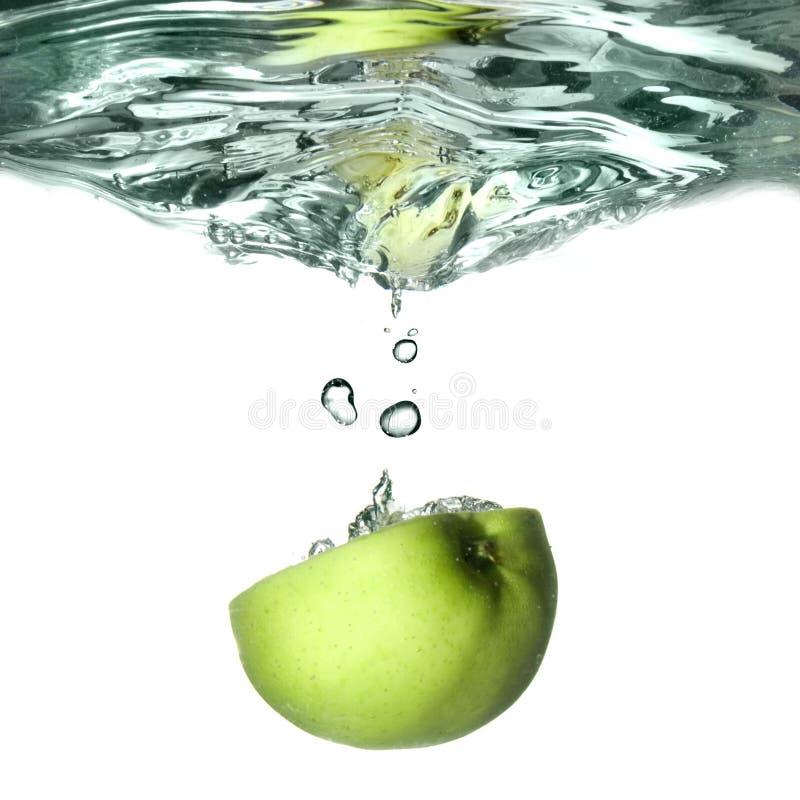 La pomme verte a relâché dans l'eau images libres de droits