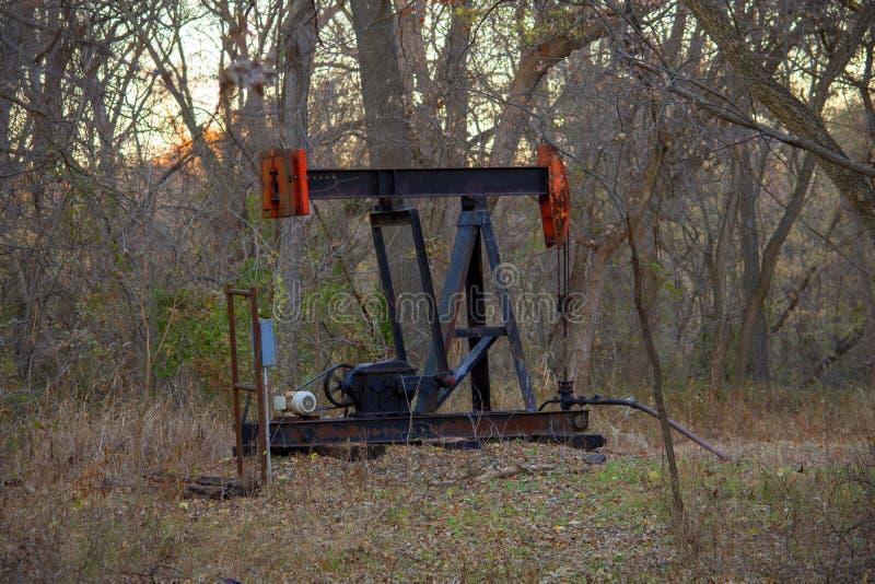 La pompa nera e rossa Jack del pozzo di petrolio fotografia stock libera da diritti
