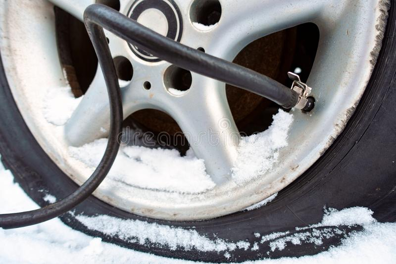 La pompe pompe l'air dans le pneu en hiver photo stock