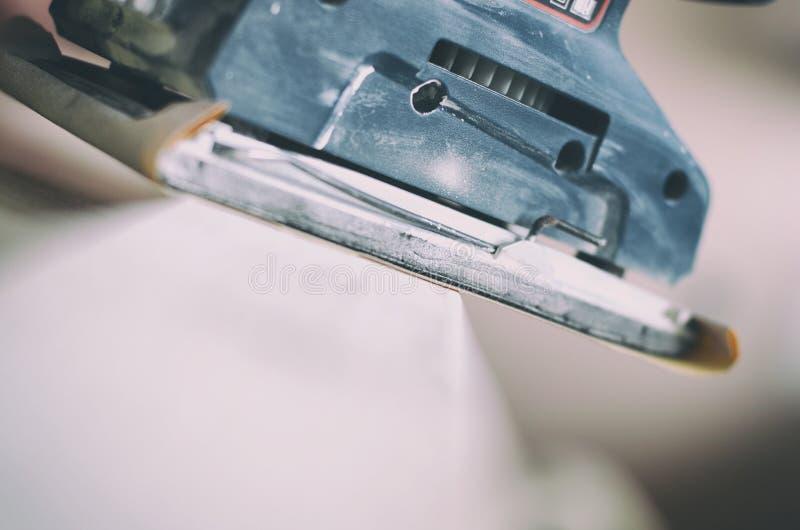 La ponceuse orbitale en service, vieille porte de ponçage pour un nouveau lèchent de la peinture photo libre de droits