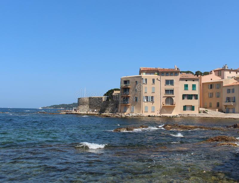 La Ponche圣特罗佩海滩 天空蔚蓝、地中海的清楚的水和历史的堡垒的石墙 免版税库存图片