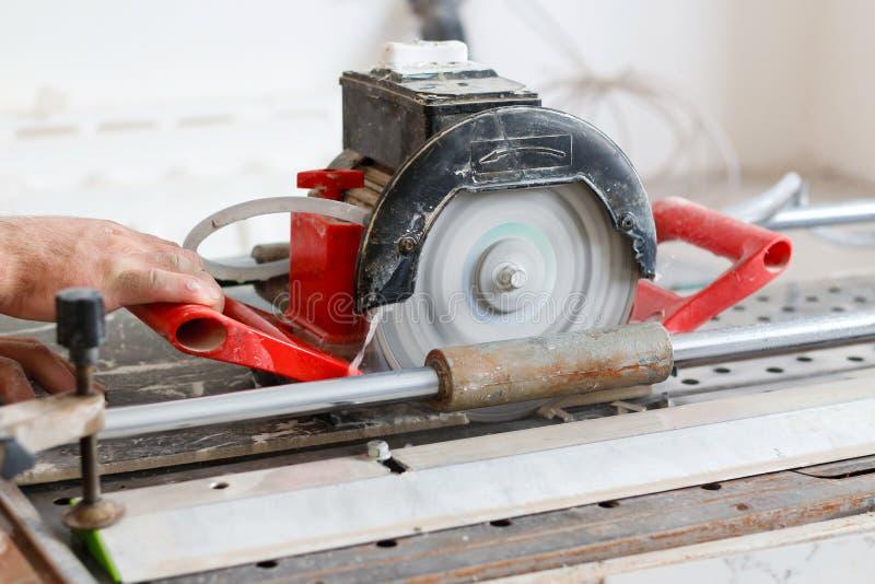 La porcelaine électrique de travailleur de la construction de carreleur d'homme coupe la tuile de tuiles photo libre de droits
