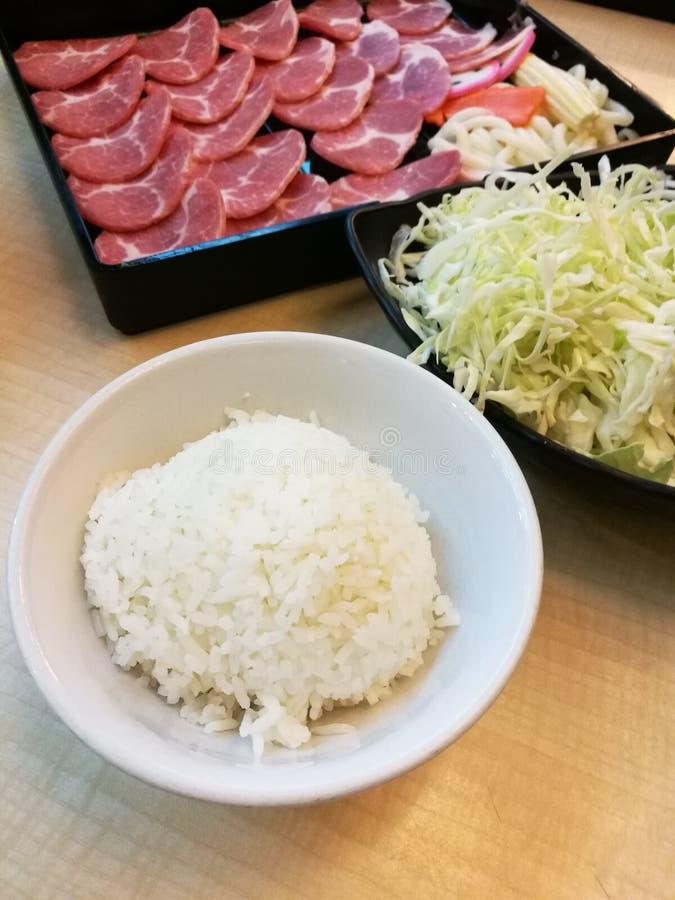 La porción del cuenco de arroz y de la bola del cerdo de pescados frescos de la rebanada y de la sonrisa en la bandeja con la col fotografía de archivo libre de regalías