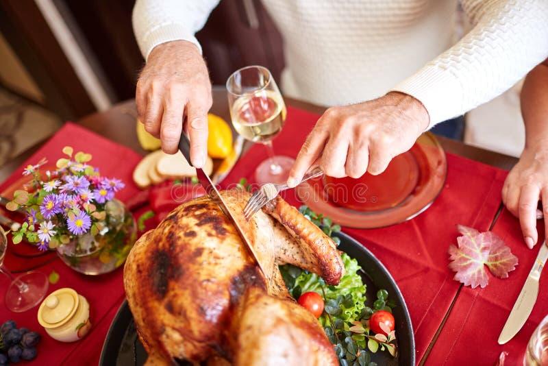 La porción del viejo hombre del primer asó el pavo en un fondo de la tabla Cena de la acción de gracias Concepto festivo tradicio imagenes de archivo