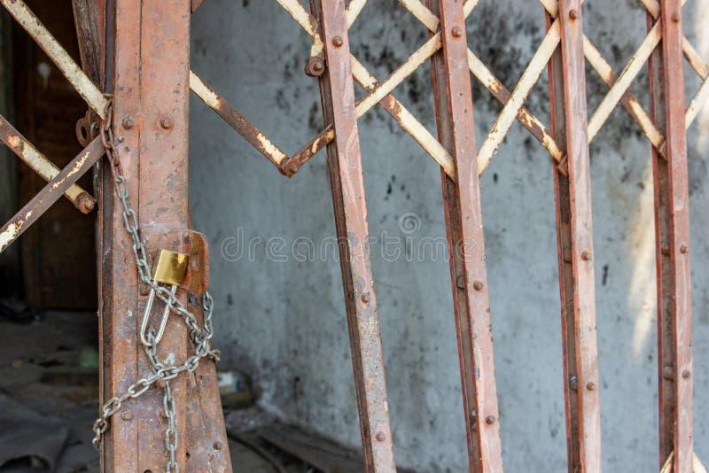 La porta d'acciaio arrugginita dello scorrevole è serratura fotografia stock