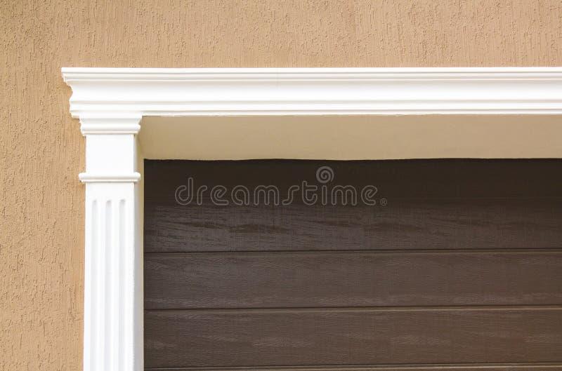 La porta del garage è decorata con un arco bianco dello stucco immagine stock libera da diritti