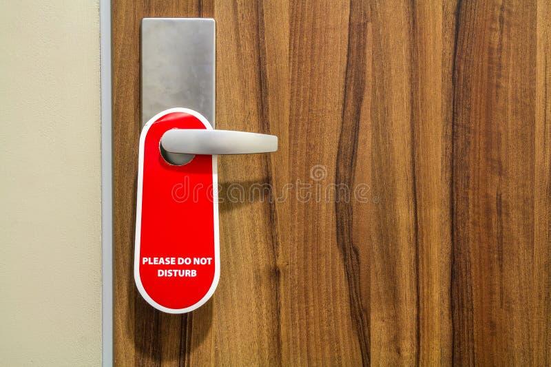 La porta di camera di albergo con il segno non disturba prego immagini stock
