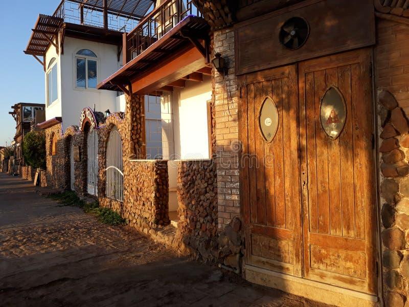 la porta di legno della costruzione ed il lato soleggiato della via in un villaggio egiziano ad alba fotografie stock libere da diritti