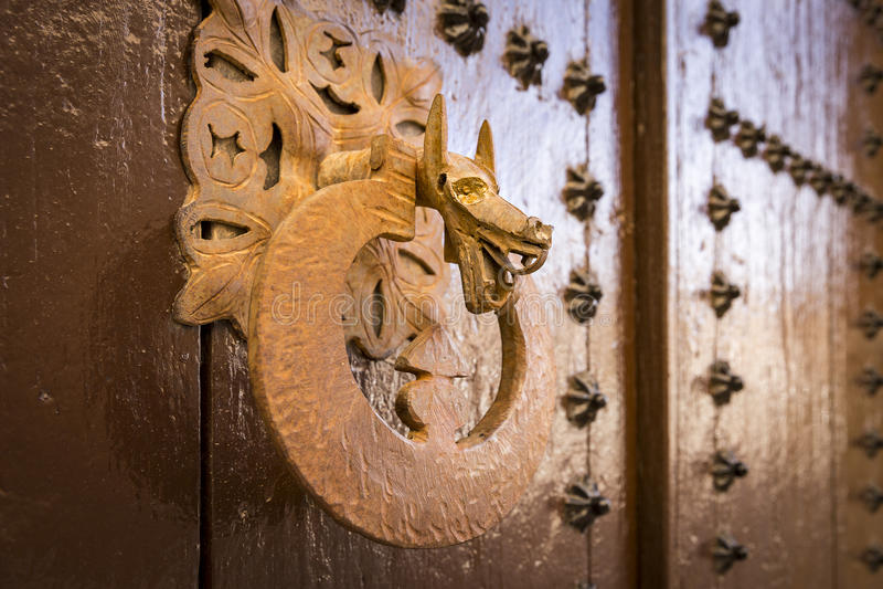 La porta di legno marrone antica con gli ornamenti metallici e una maniglia a forma di come drago si dirigono immagini stock libere da diritti