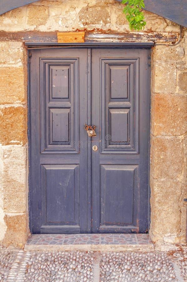 La porta di legno scura chiusa moderna su cemento giallo ha strutturato la casa immagine stock