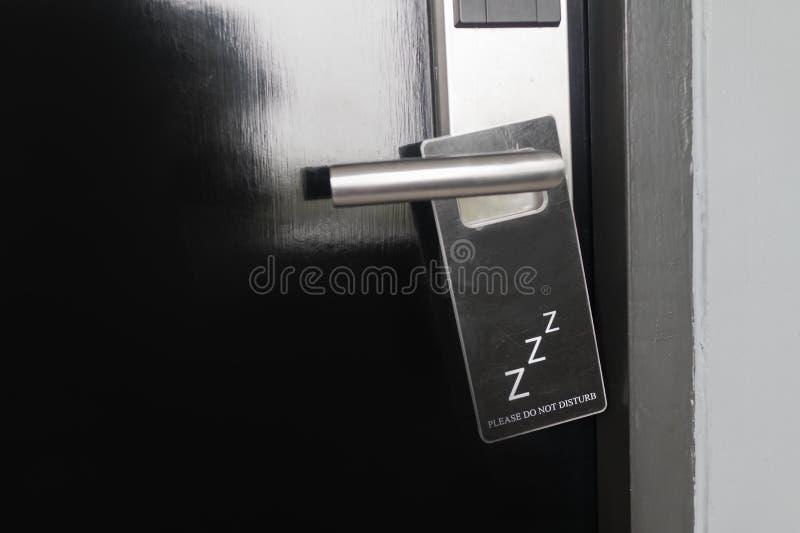 La porta nera chiusa di camera di albergo con prego non disturba il segno sulla maniglia di porta fotografie stock libere da diritti